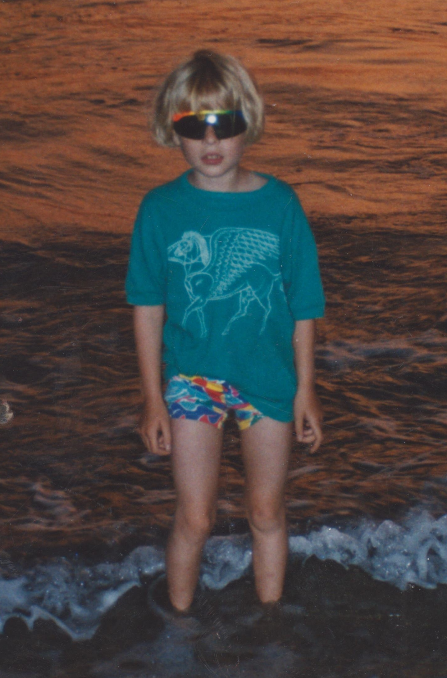 Rosie, at the age of 6, stands in the sea at sunset