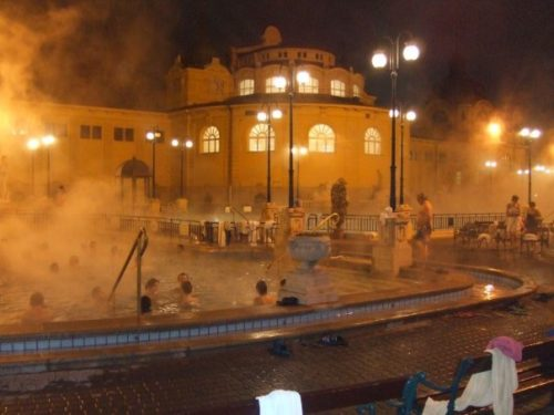 A photo of the Széchenyi Baths at night showing a steaming pool in the foreground with the neo-baroque yellow building in the background