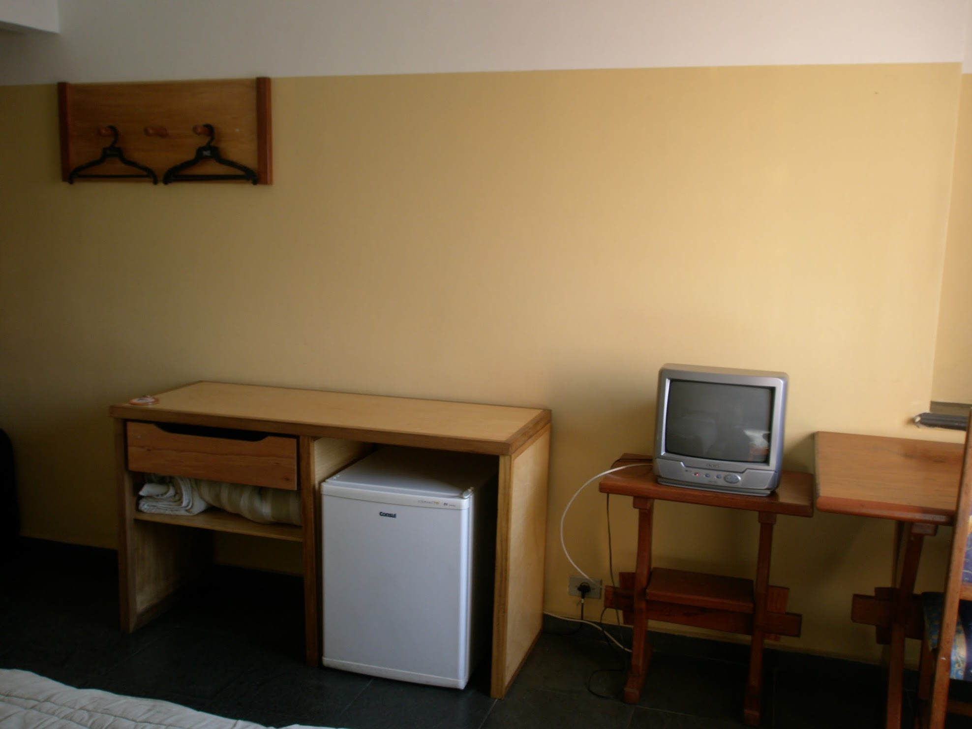 A yellow wall of a hostel room. A table and drawer with under counter fridge. A a grey TV on a stand. Hangers on hooks on higher on the wall.