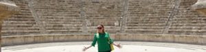Rosie standing with jazz hands, wearing a green top and sunglasses in front of Amman Roman Amphitheater in Jordan