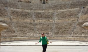 Rosie standing with jazz hands, wearing a green top and sunglasses in front of Amman Roman Amphitheatre in Jordan