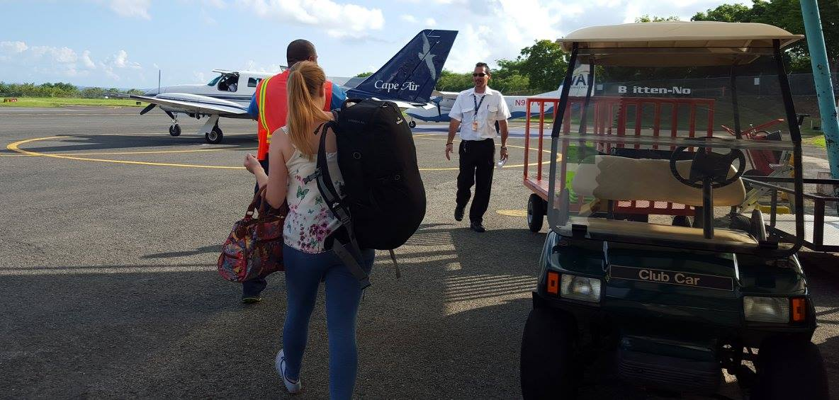 Cape Air plane waits on the tarmac, and Rosie carries her bag.