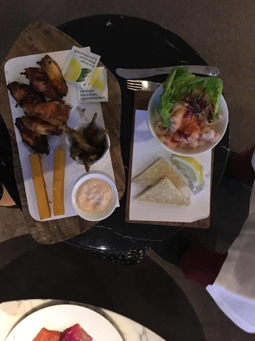 A photo of Chicken wings, prawn cocktail, courgette sticks, polenta chips, taken from above on 2 small wooden boards.
